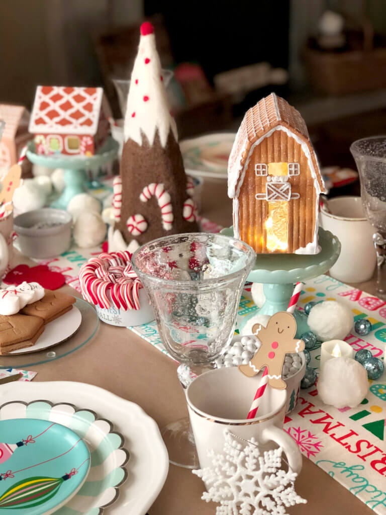 Gingerbread barn centerpiece on decorated table for a Christmas Cookie Exchange Party