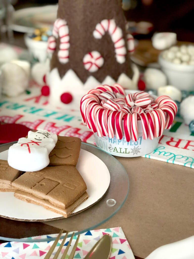 Bowl of candycanes and mini gingerbread house pieces for a Christmas Cookie Exchange Party