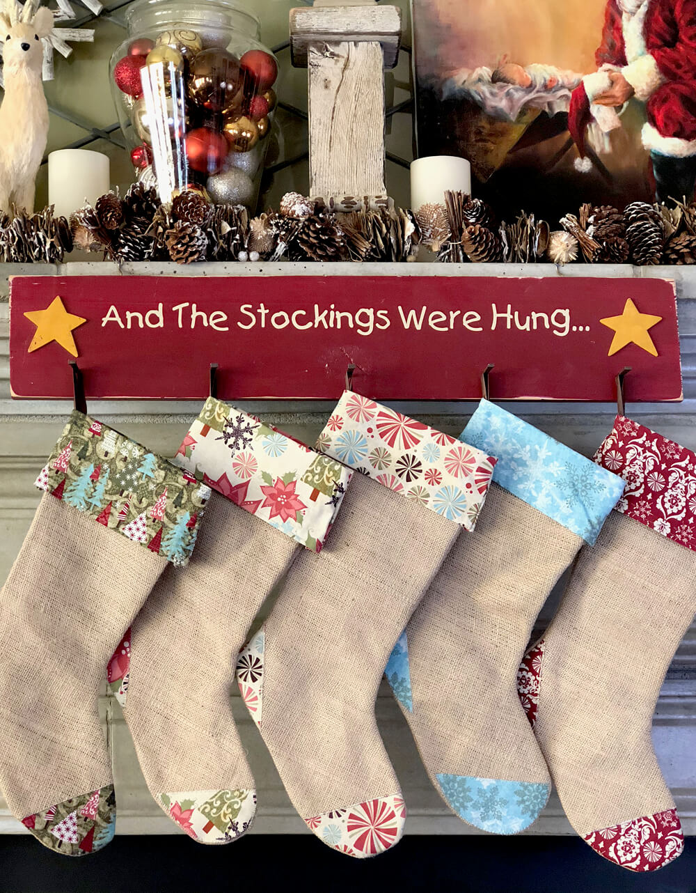 And the stockings were hung sign with burlap stockings on a rustic woodland Christmas mantel