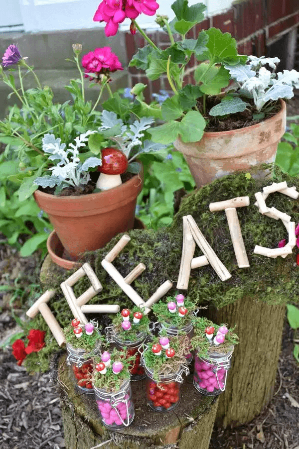 Tree stumps with moss and flower pots with toad stool favors for top party trends