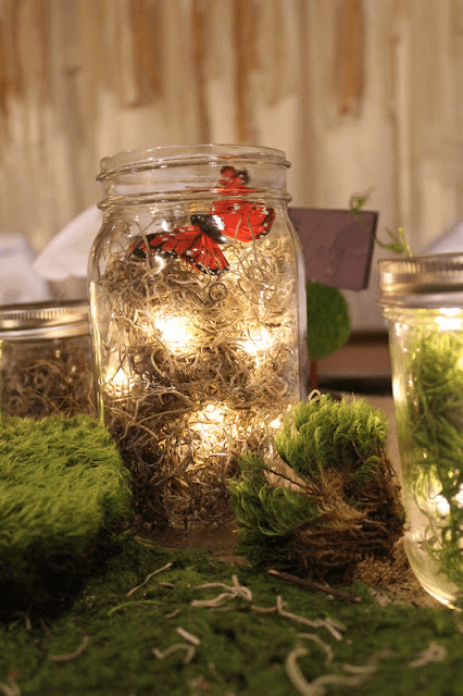 mason jar luminary with moss and butterfly for woodland party a top party trend
