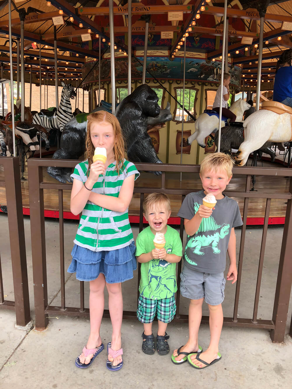 Kids at the zoo in front of carousel eating ice cream cones