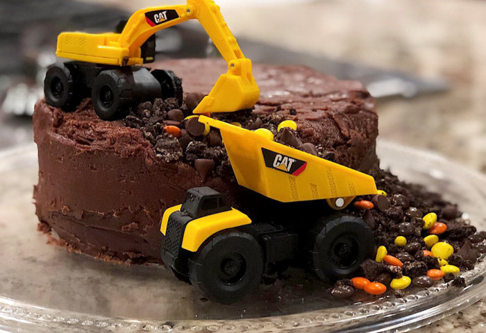 Construction trucks digging into brownie cake for Boys construction birthday party