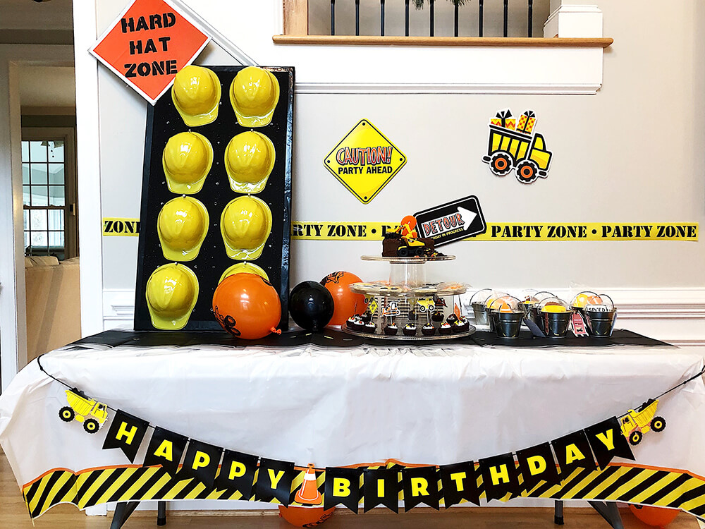 Treat table with hard hat wall and signage for Boys construction birthday party