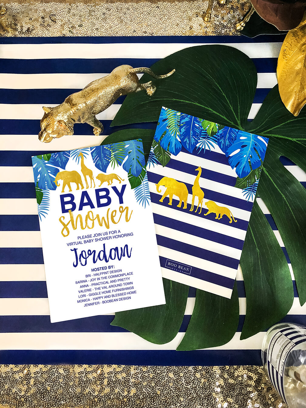 Invitation for a glam safari baby shower on striped table runner