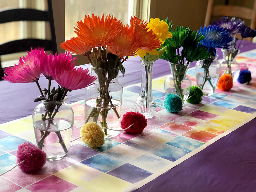 Rainbow hued flowers on watercolor runner table for over the rainbow party