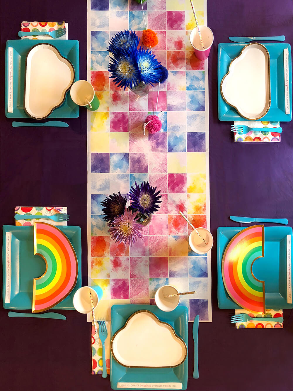 Rainbow flowers and plates on watercolor runner table for over the rainbow party