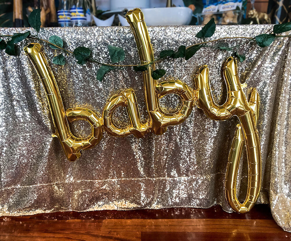 Baby script balloon on sequin backdrop for a Cupcakes with jungle animal topper and leaf wrappers for a glam safari baby shower