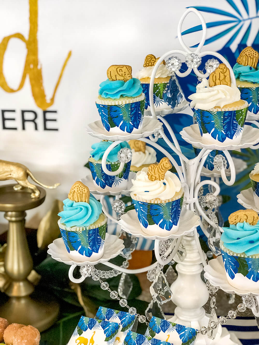 Cupcakes with jungle animal topper and leaf wrappers for a glam safari baby shower