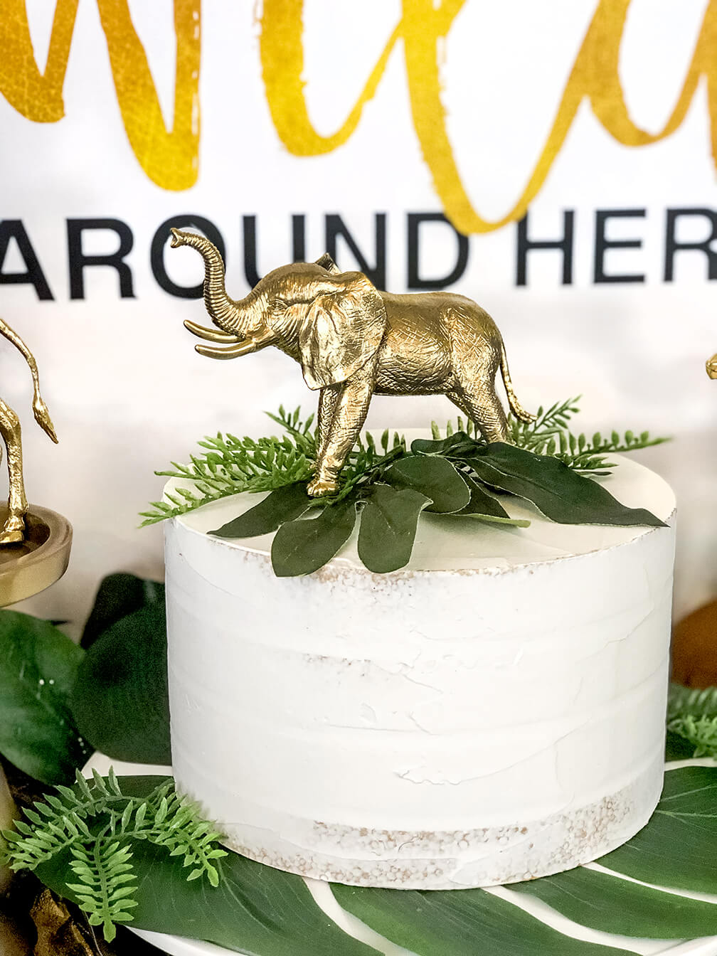 Golden elephant cake topper for a glam safari baby shower