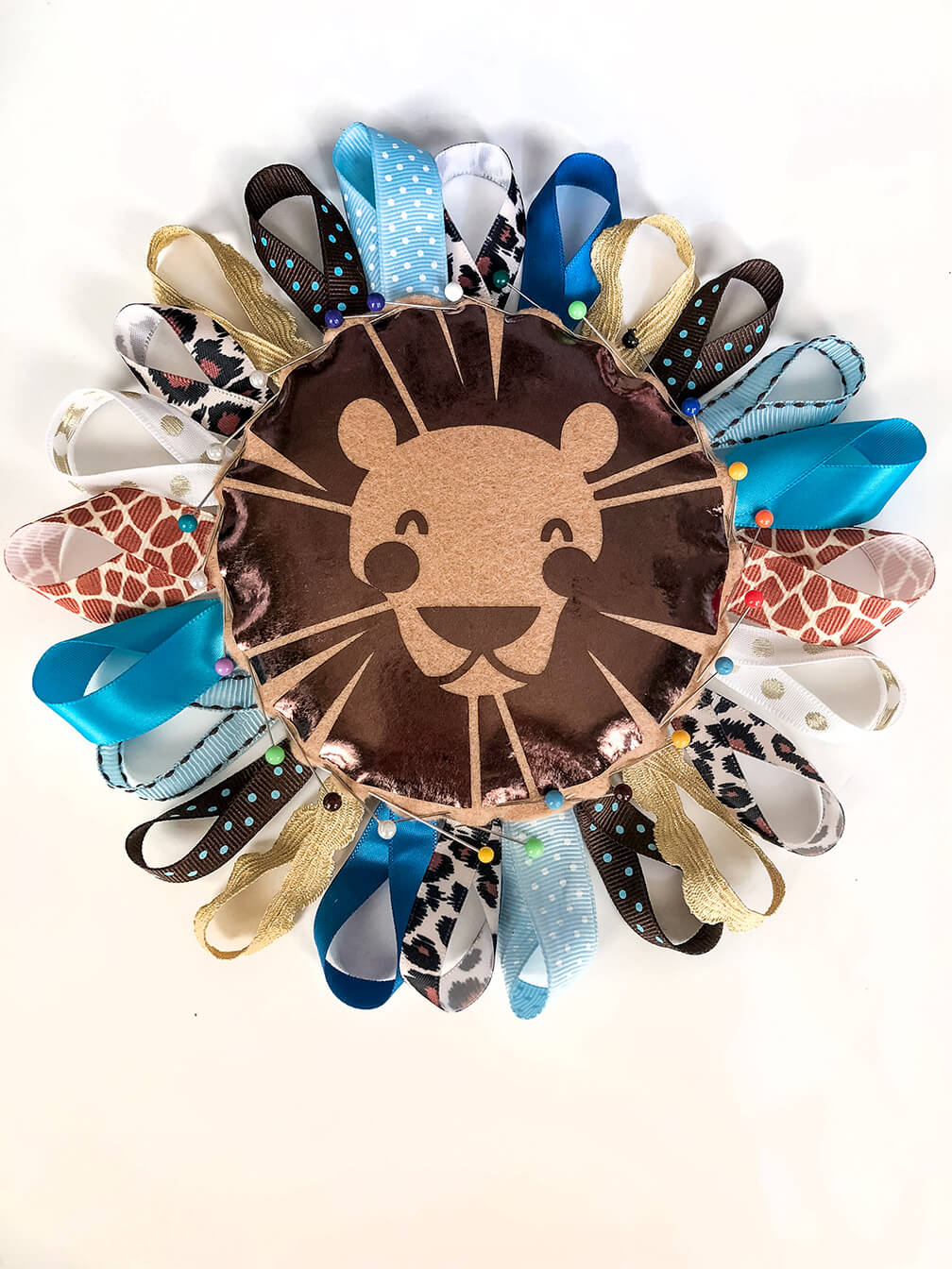 Carefully pinned ribbons onto the outside edge of Lion Baby Tag Toy DIY