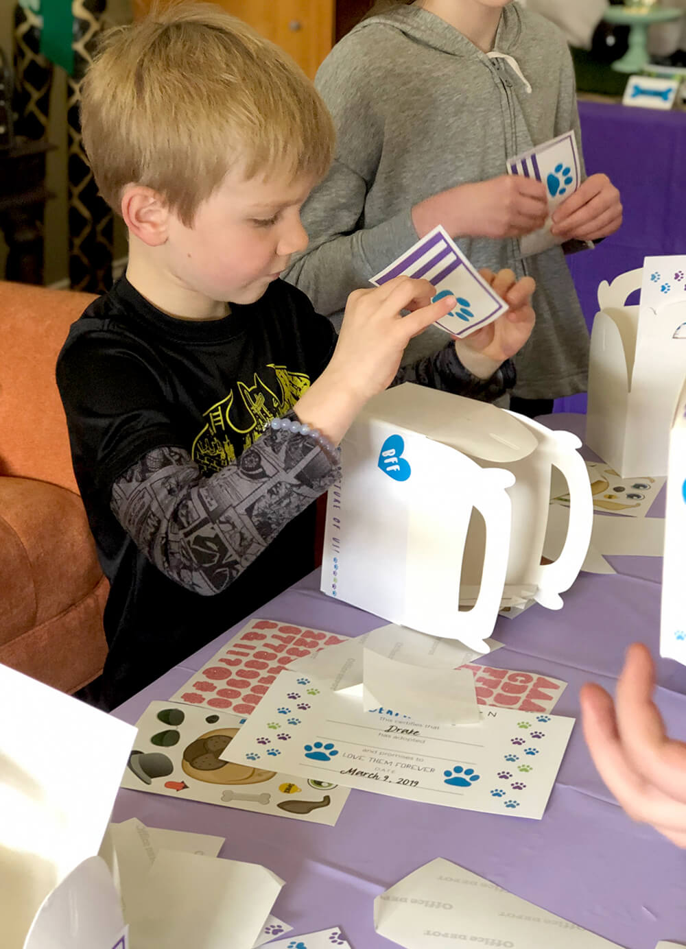 Applying stickers to favor box - Puppy party activity ideas for kids