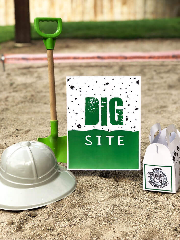 Can U Dig It? balloons over a dino dig party activity sand pit site.