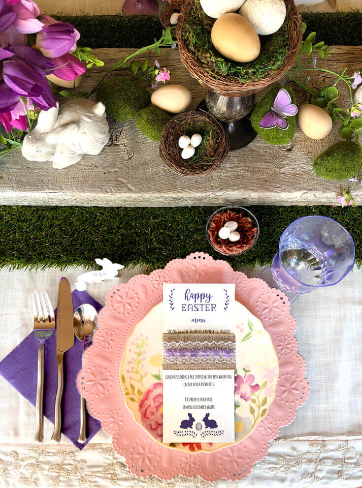 Fully decorated table for Easter dinner. Grass runner with rustic wood board, moss, bunnies, butterflies, and tulips.