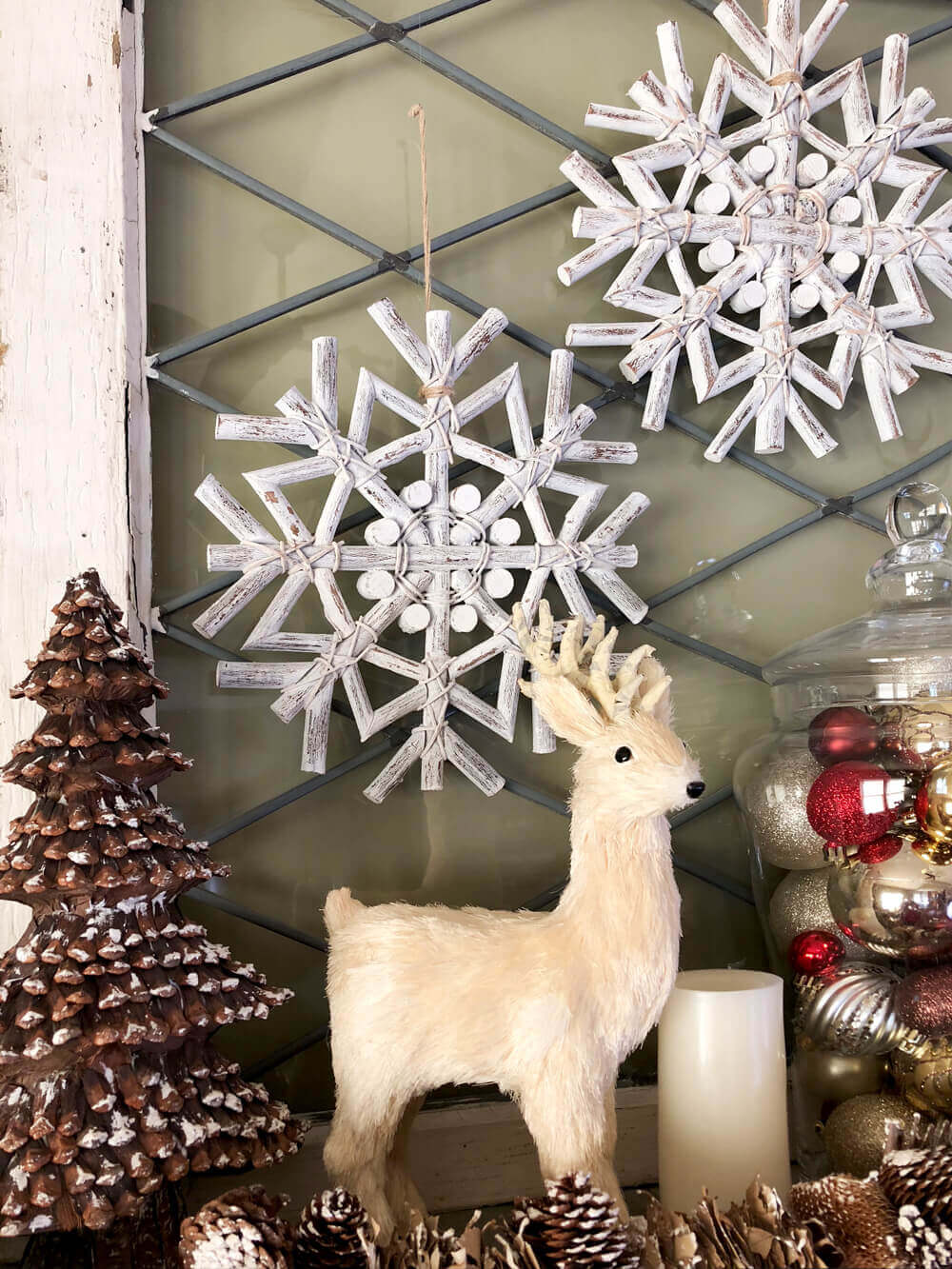 Deer, snowflakes, and tree on a rustic woodland Christmas mantel