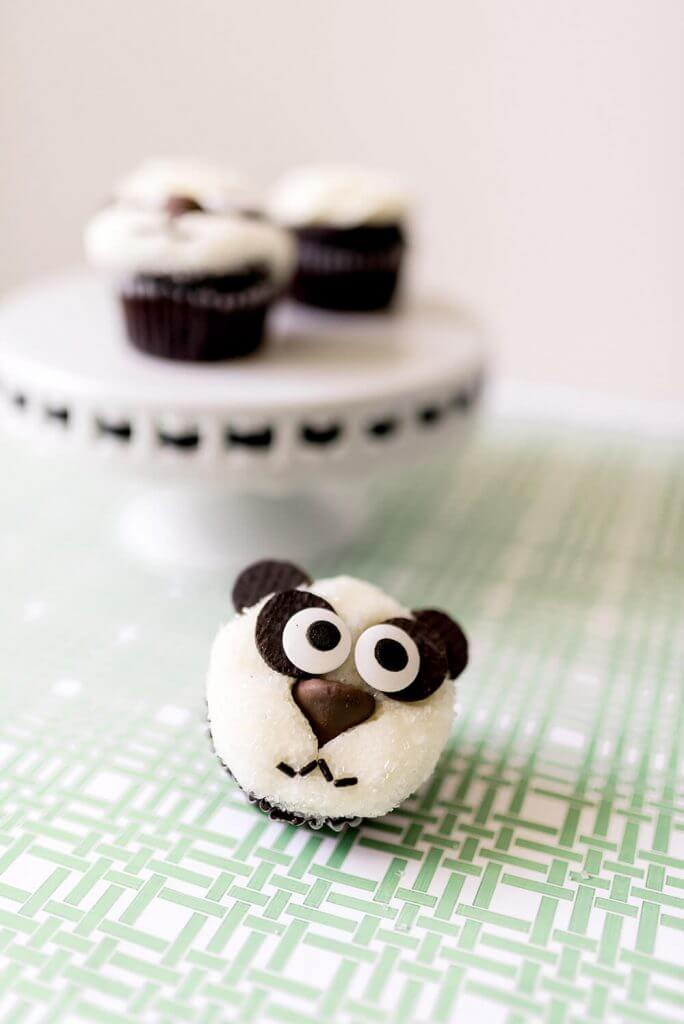 Panda party cupcake in front of a tray of more cupcakes for Panda themed birthday