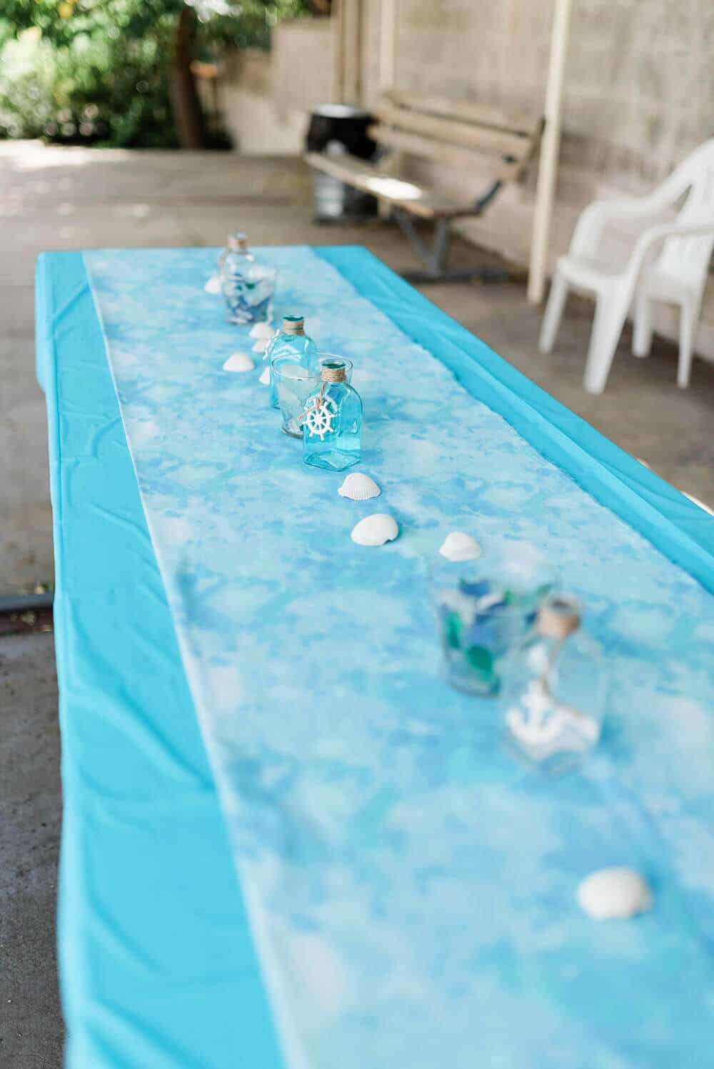Water print fabric runner, shells, and sea glass centerpieces
