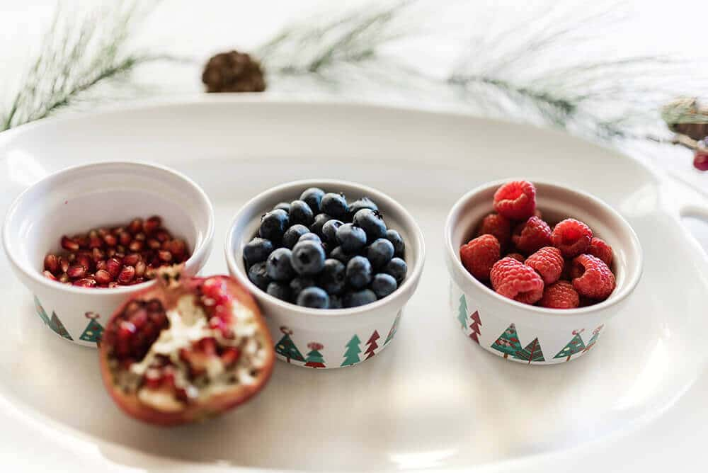 Bowls of berries and pomegranate on tray