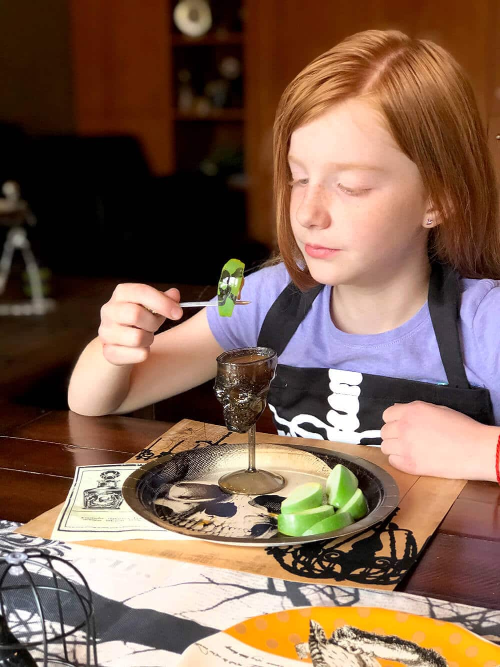 Girl dipping poison apple slices into caramel