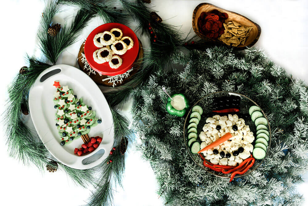 Fruit Christmas tree, thumbprint cookies, and veggie snowman on table