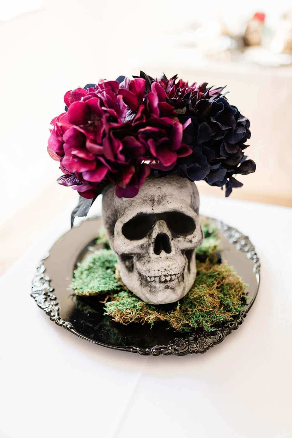 Finished Floral Skull Centerpiece on black charger and bed of moss