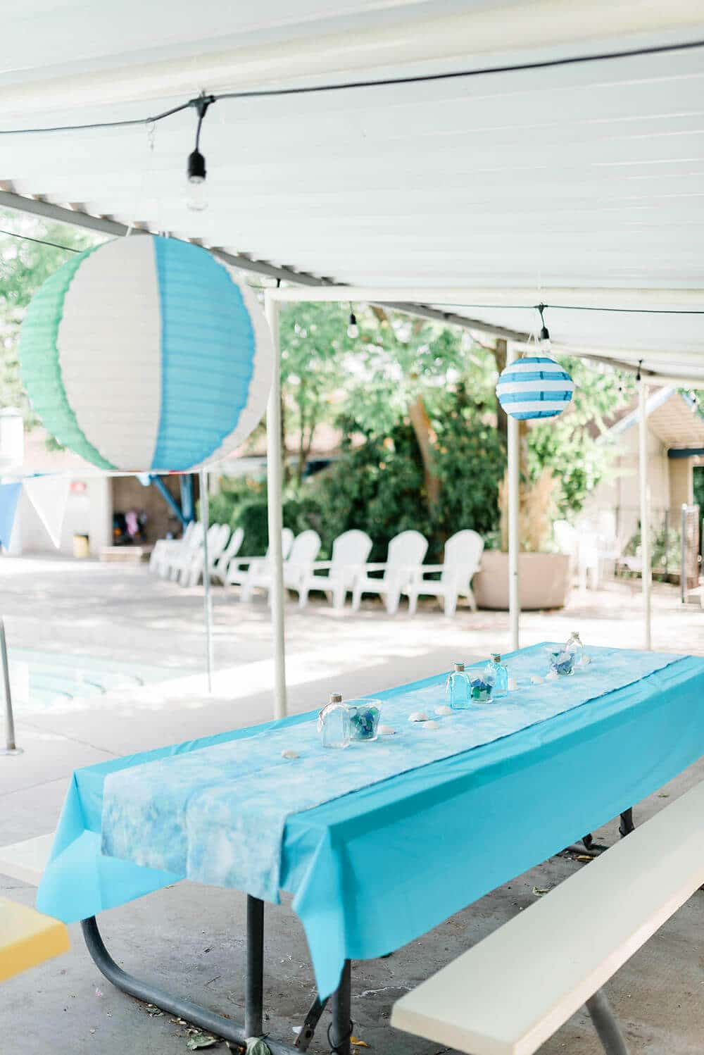 Pool party table decor with hanging lanterns