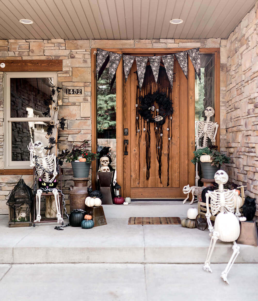 Halloween porch decorated with skeletons and white pumpkins
