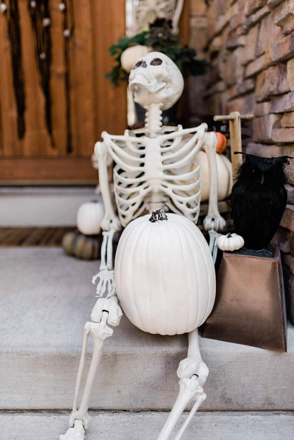 Skeleton holding white pumpkin