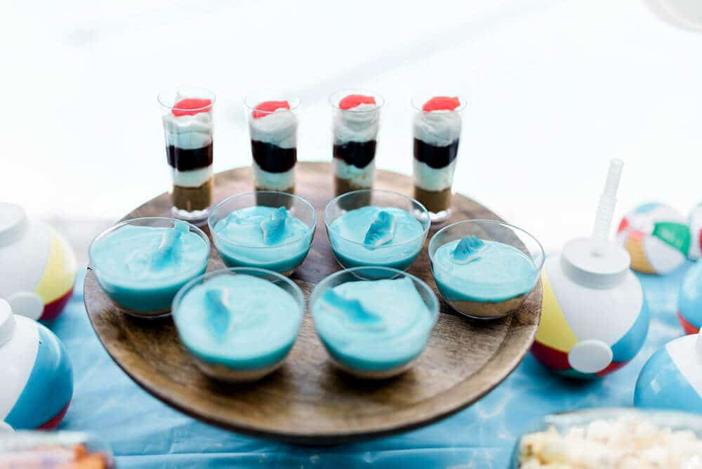 Raspberry cheesecake shooters and shark pudding cups on pool party table