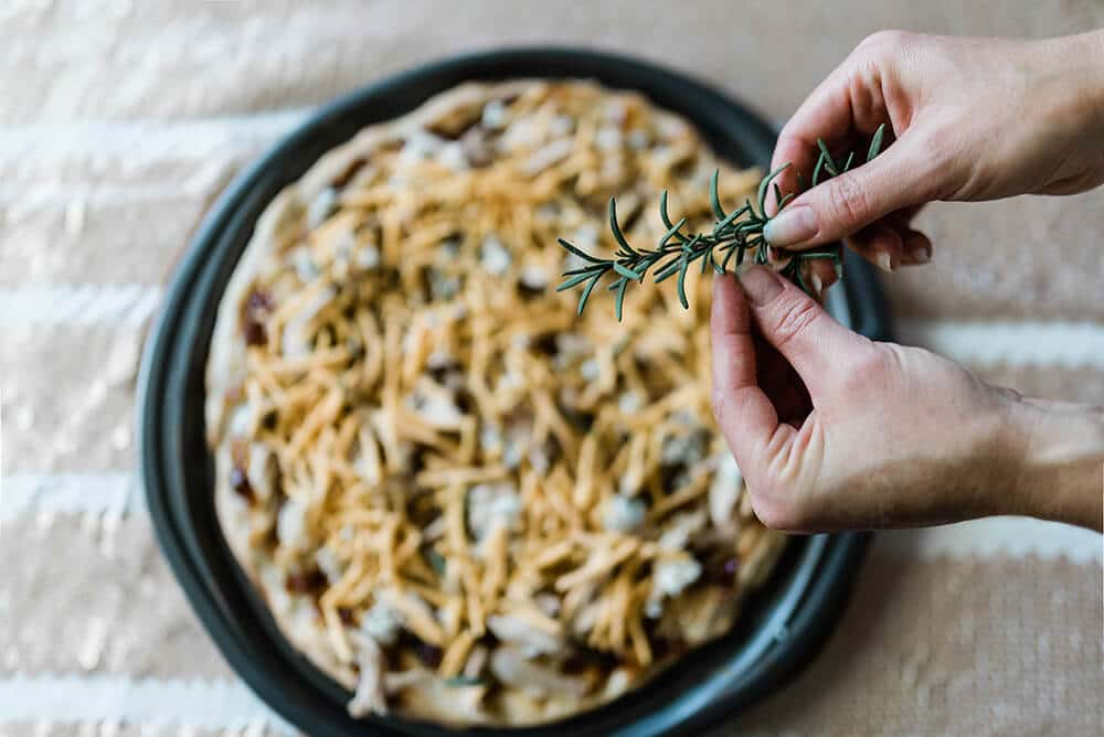 Adding fresh rosemary to fig pizza