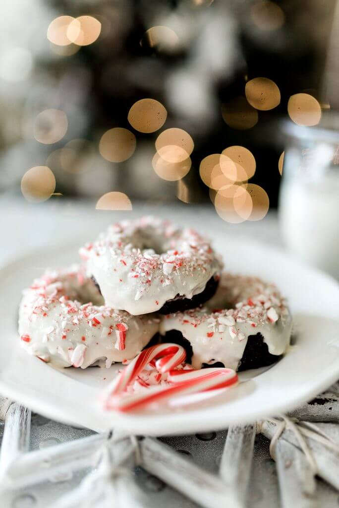 Candy canes making heart in front of plate of glazed chocolate donuts