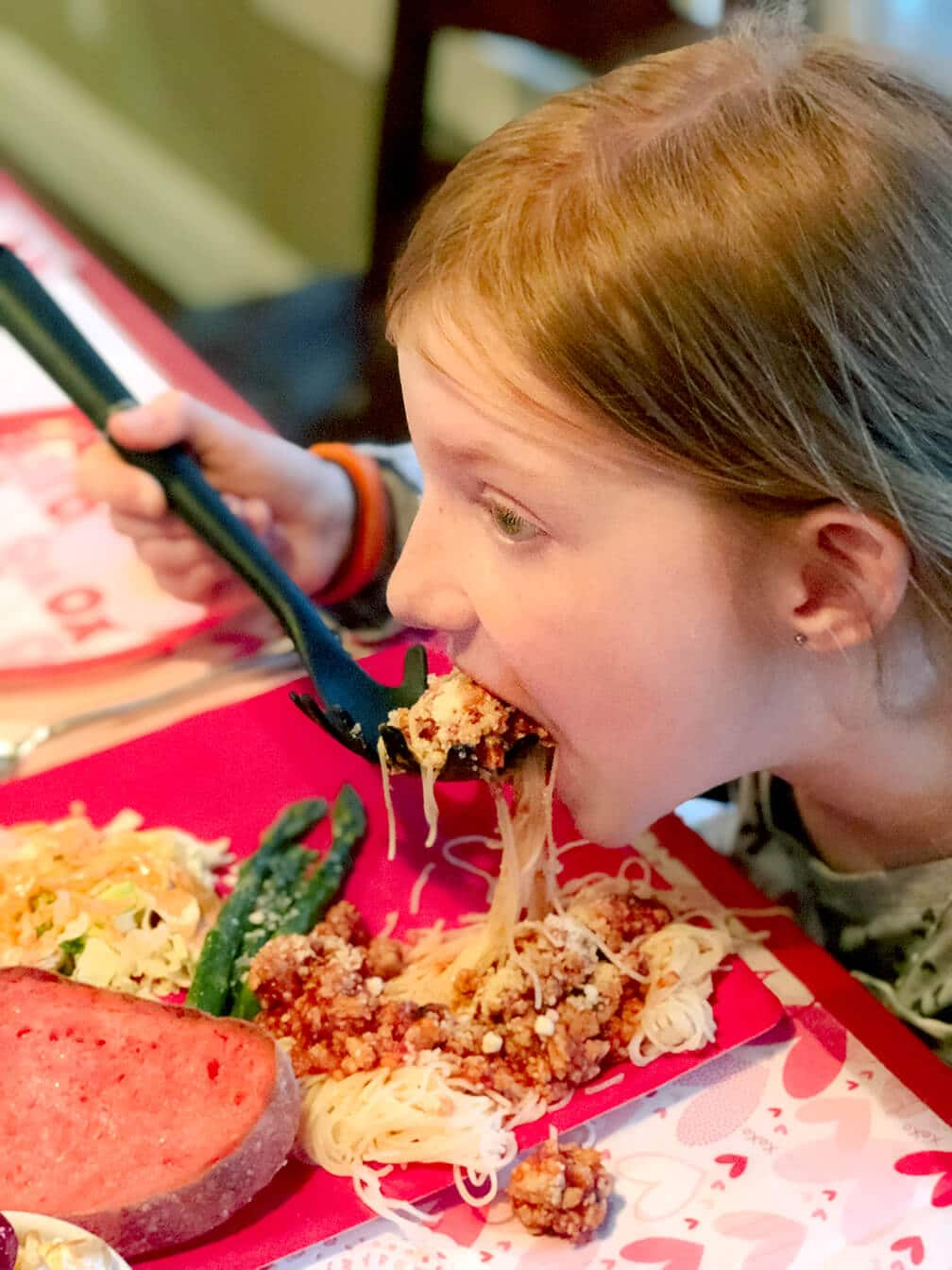 Girl eating spaghetti dinner with pasta spoon