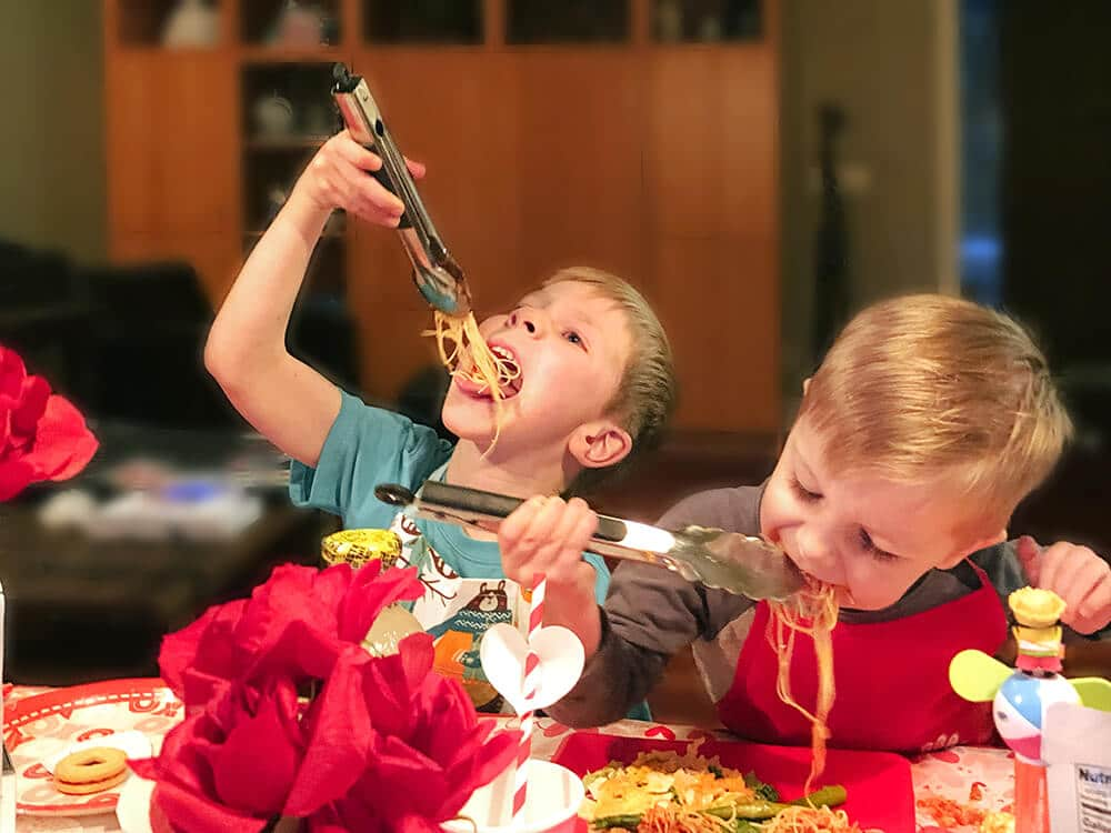 Two boys eating spaghetti dinner with tongs by Salt Lake Party Stylist