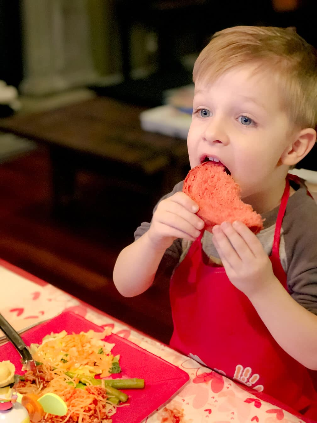 Little boy eating piece of red bread at Valentine's Dinner