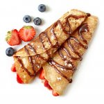 Yummy crepes rolled up with berries and chocolate