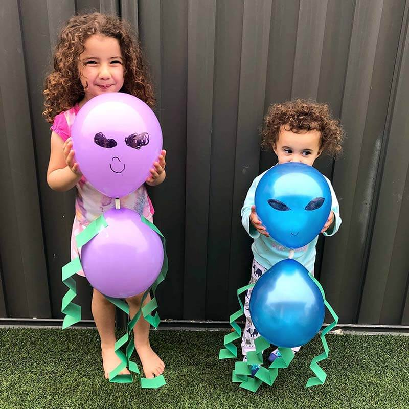 Girls holding balloon aliens