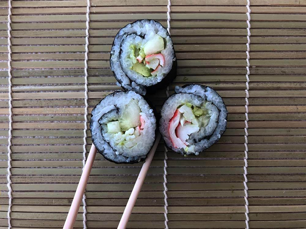 California roll pieces on mat with chopsticks by Salt Lake Party Stylist