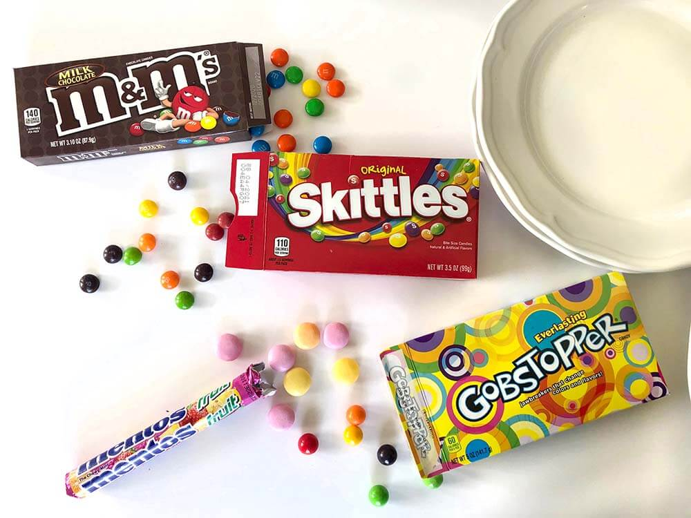 M&Ms, Gobstoppers, Mentos, and Skittles Rainbow experiment on table