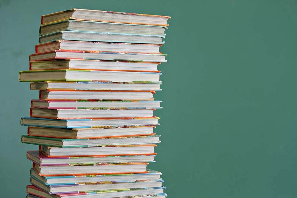 Tall stack of childrens book in a classroom