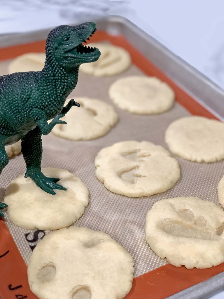 Toy T-Rex making foot imprint in a baked sugar cookie