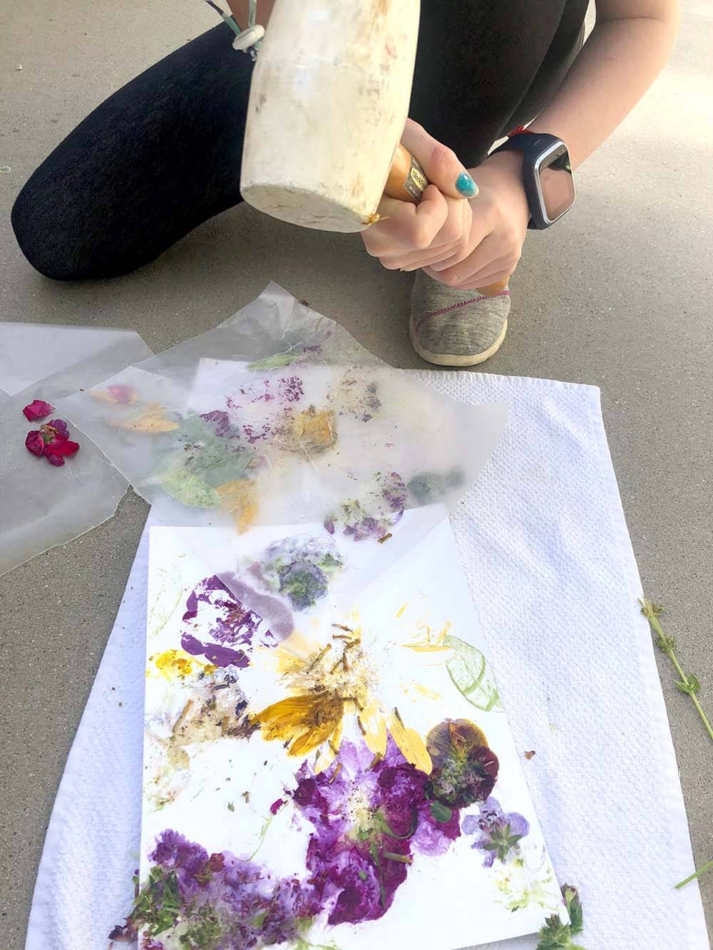 Hammering flowers through wax paper to create a floral art print