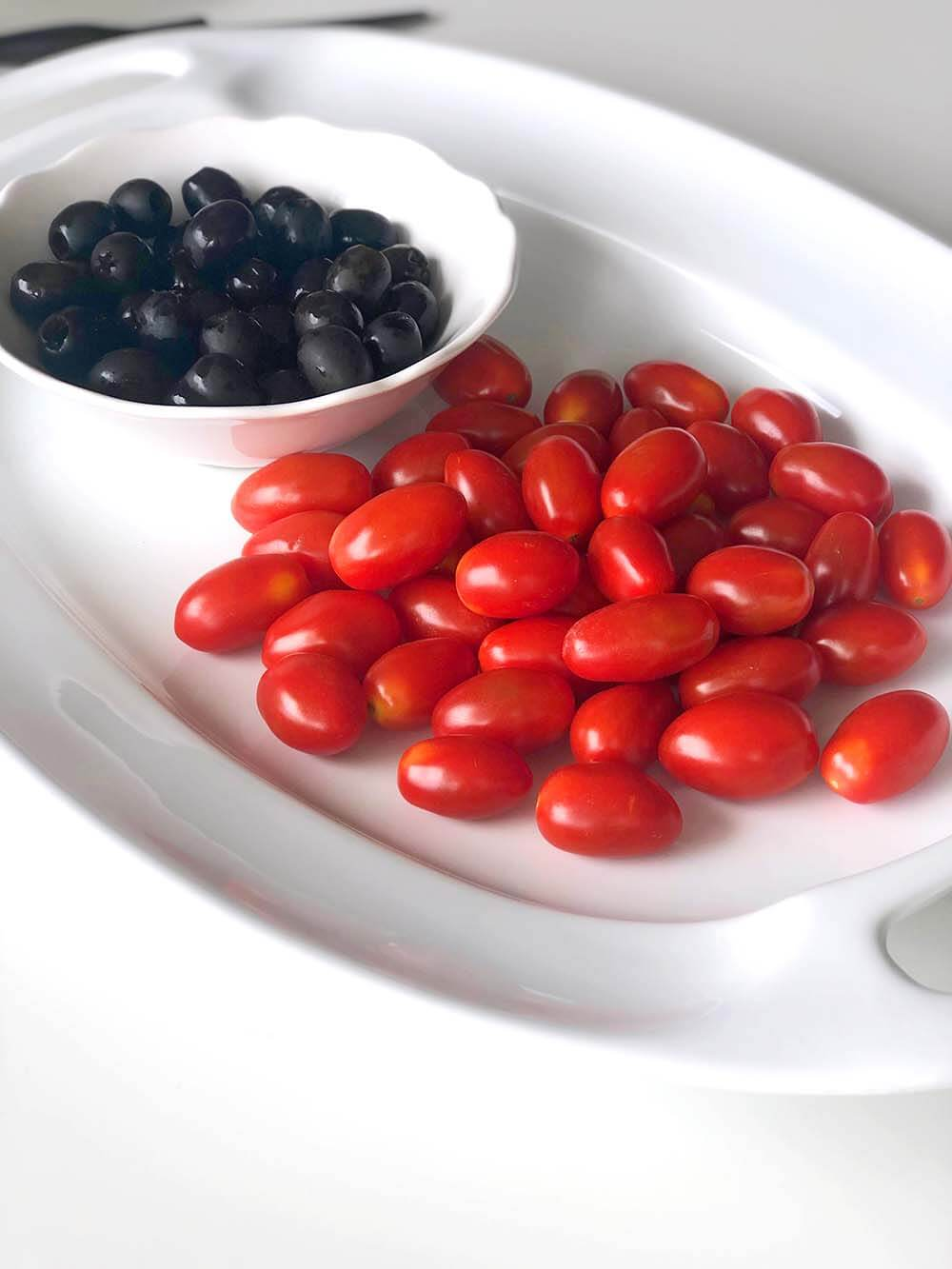 Grape tomatoes and black olives in white bowl on tray