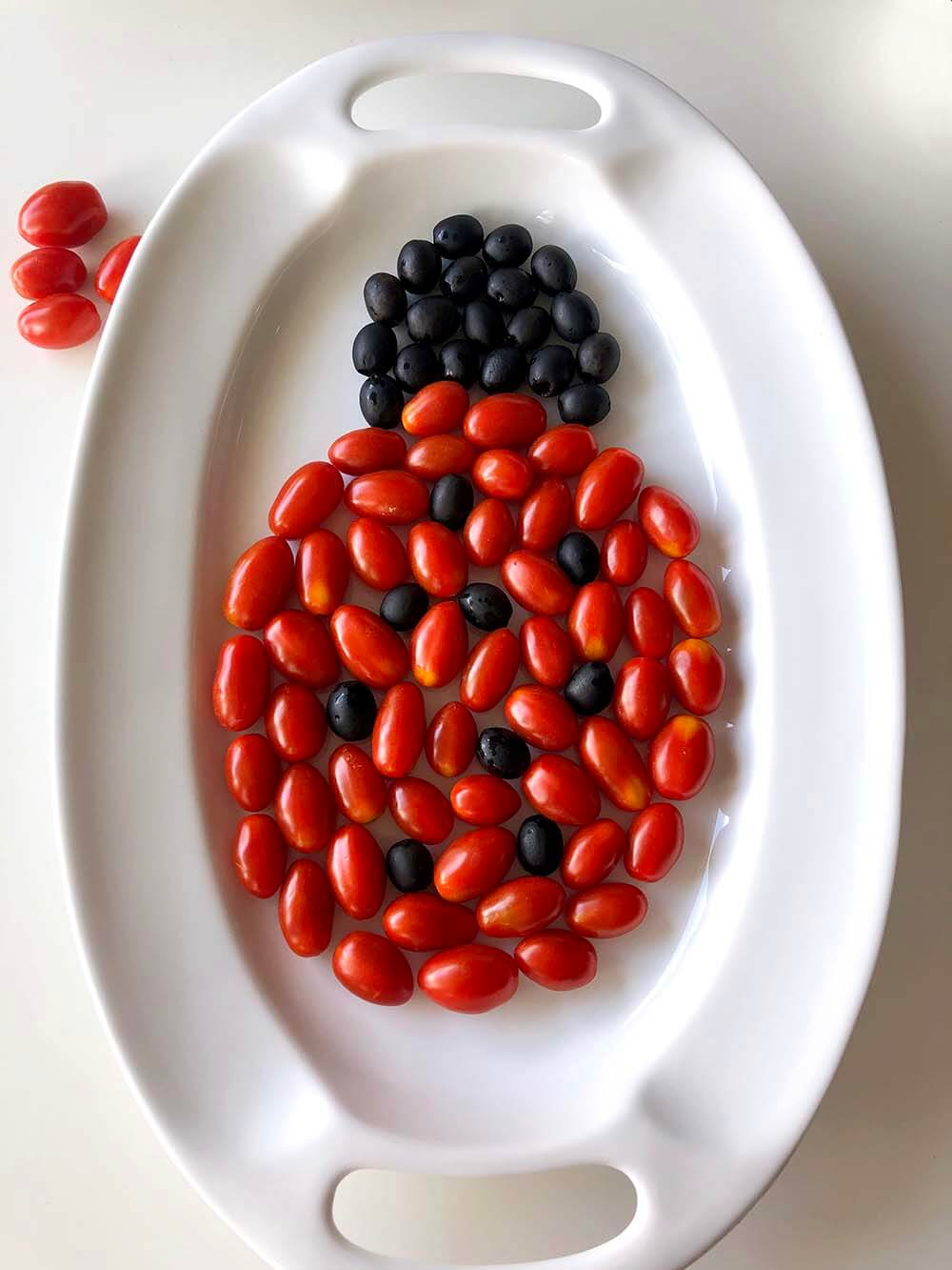 vegetable ladybug with tomato body and olive spots on white tray