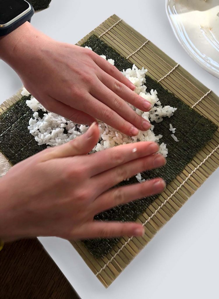 Rolling sushi at home, child spreading rice on seaweed