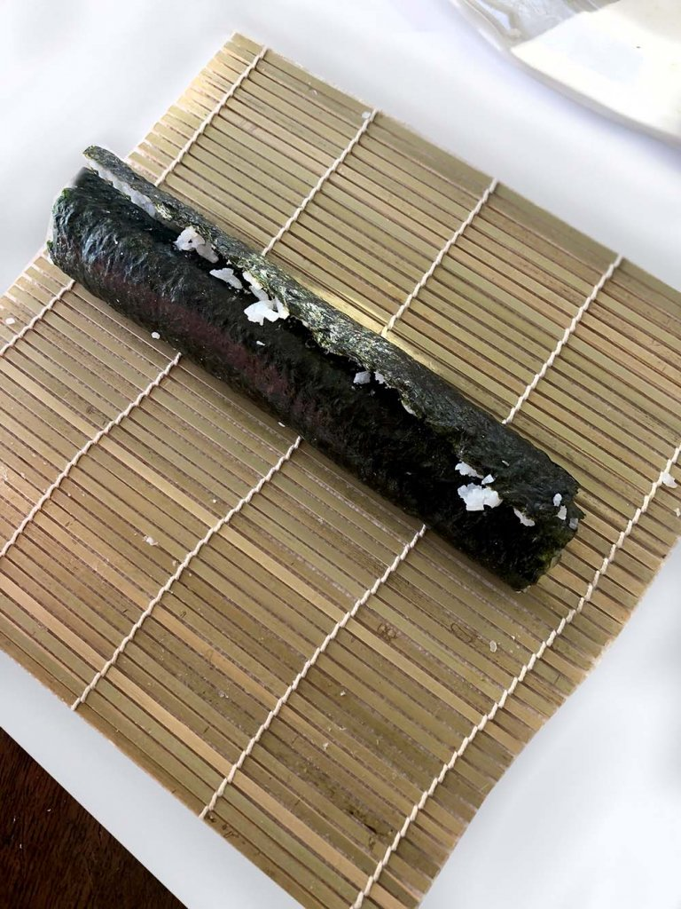 Rolling sushi at home. Finished California Roll with Seaweed wrap