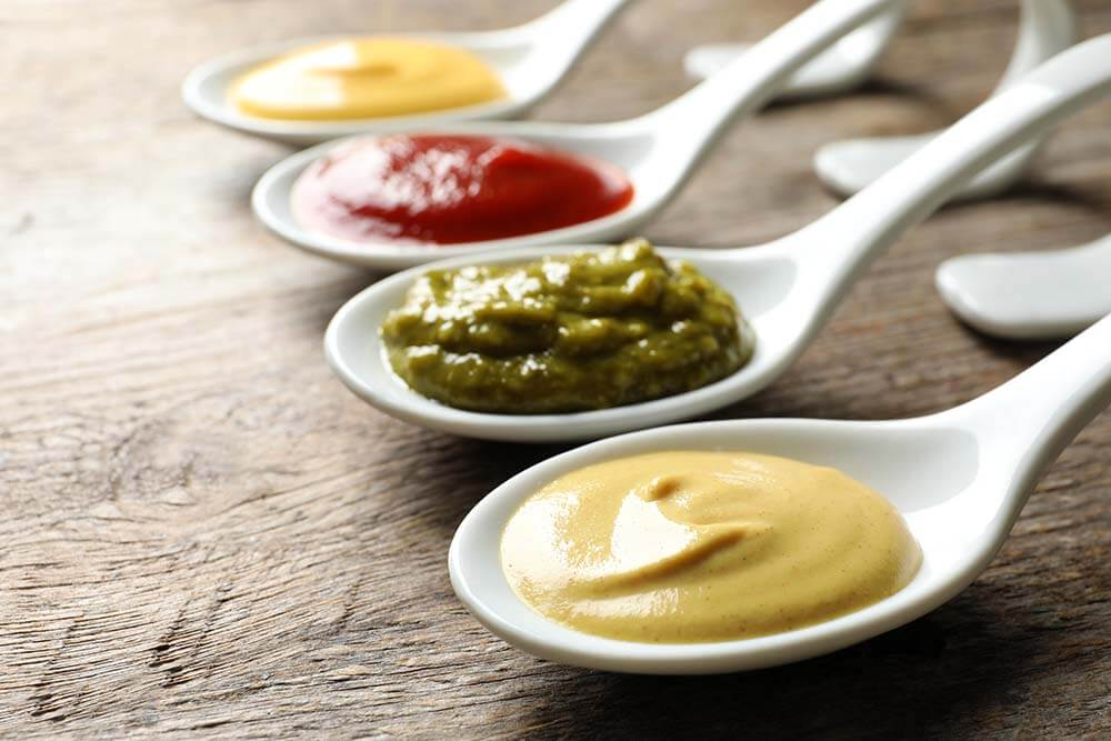 Condiments on individual spoons for safe social distancing event