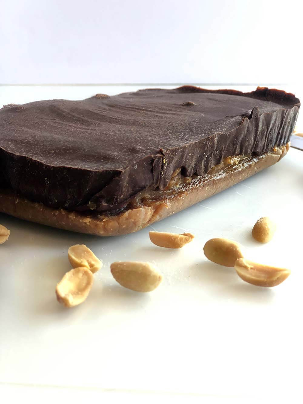 Side of homemade snickers bar on table after being removed from glass pan