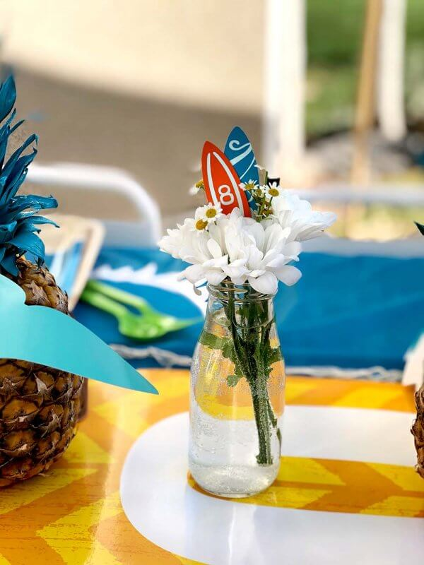 Easy flower centerpiece in milk bottle with surfboard cupcake toppers