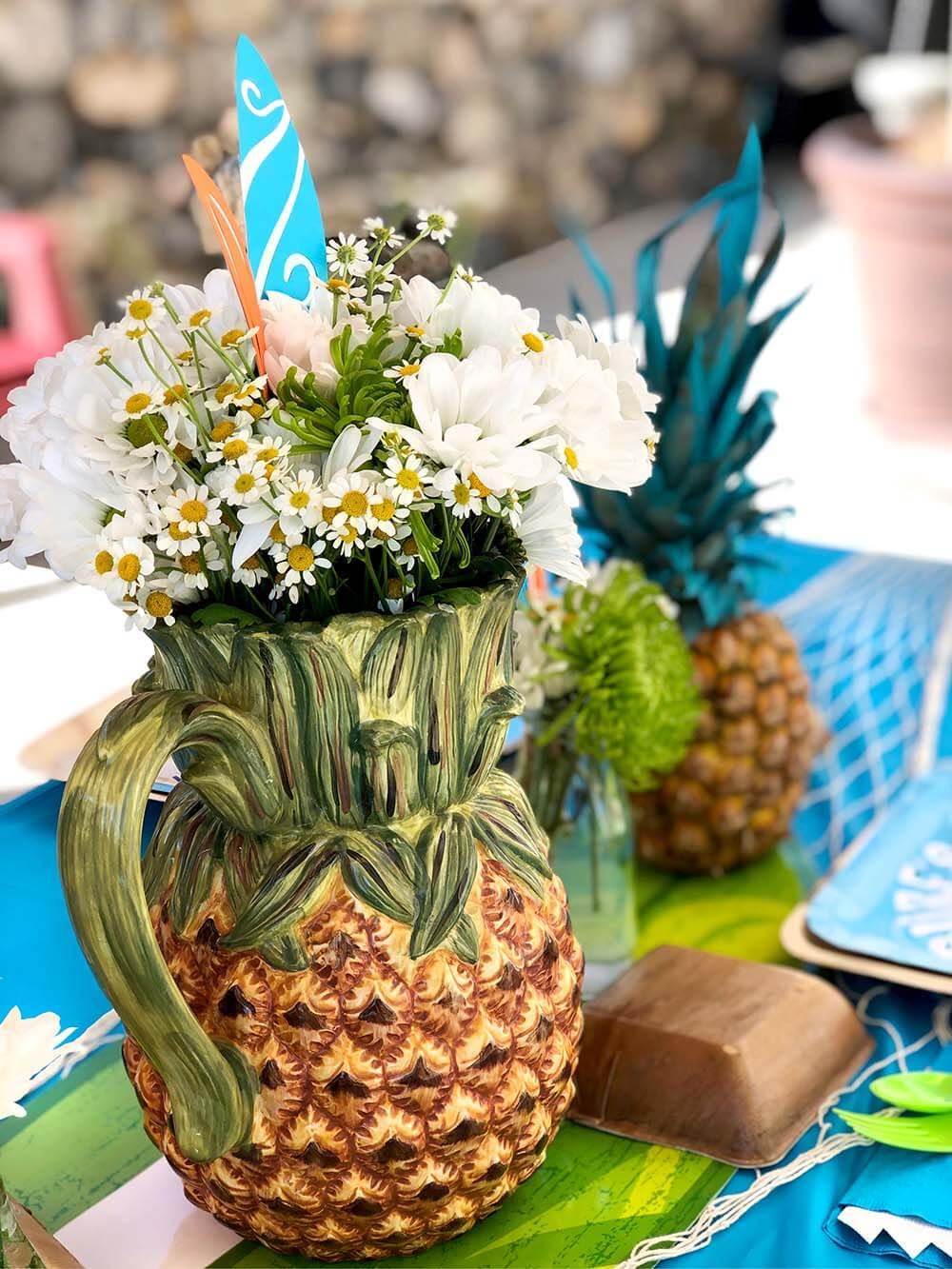 Easy floral centerpiece in pineapple pitcher for surf themed party