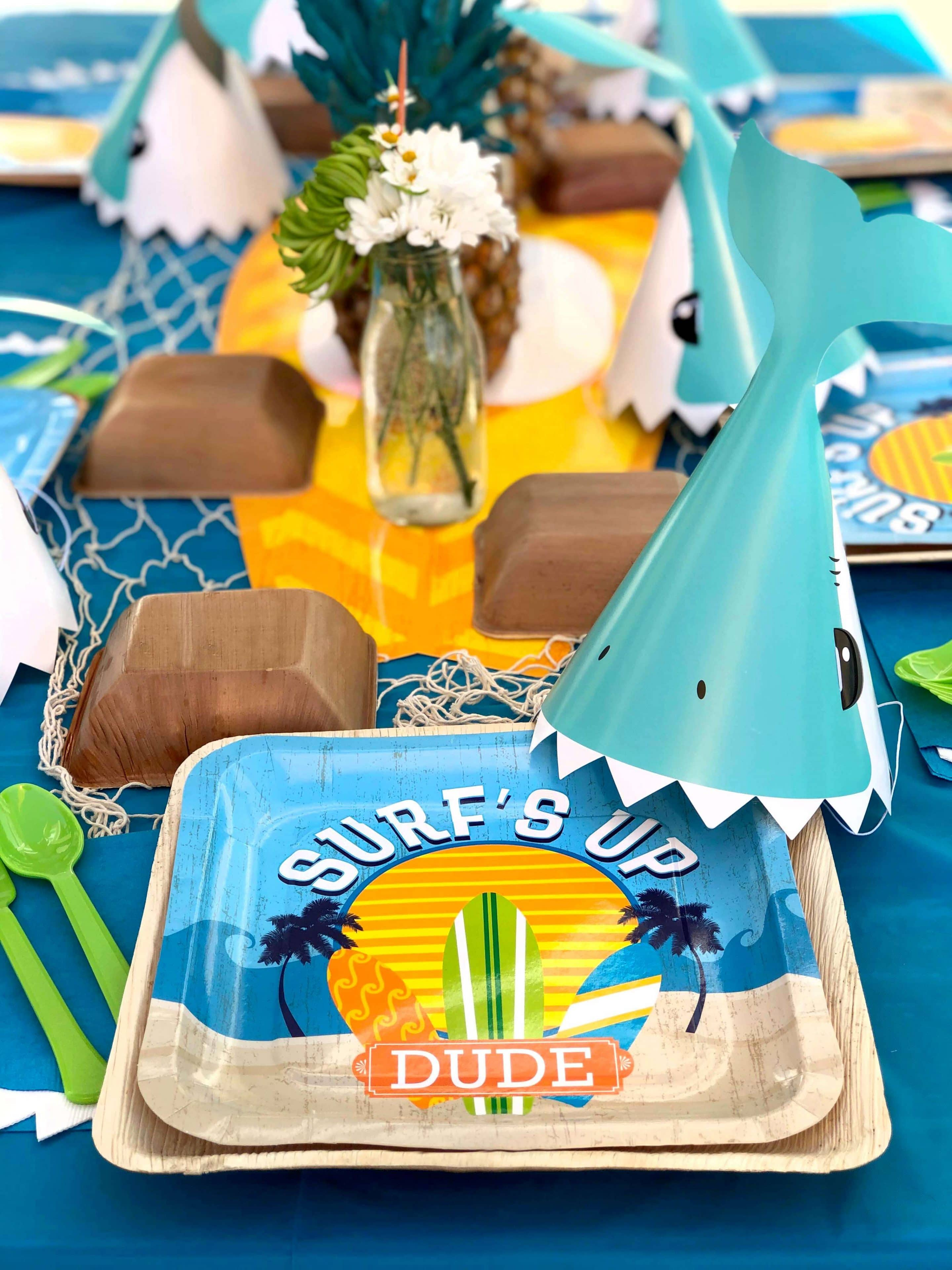 Surf party table set with pineapples and shark hats